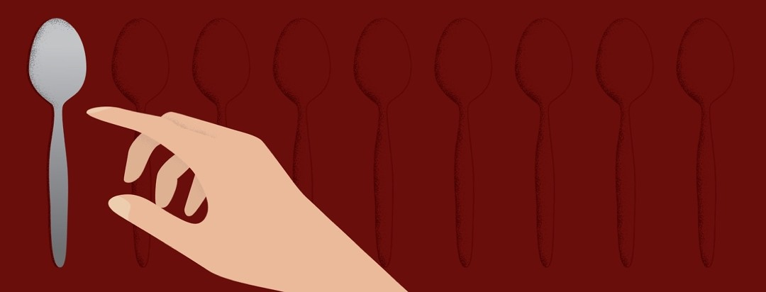 Hand reaching for the last spoon in a row. The spoon theory can be used to describe narcolepsy